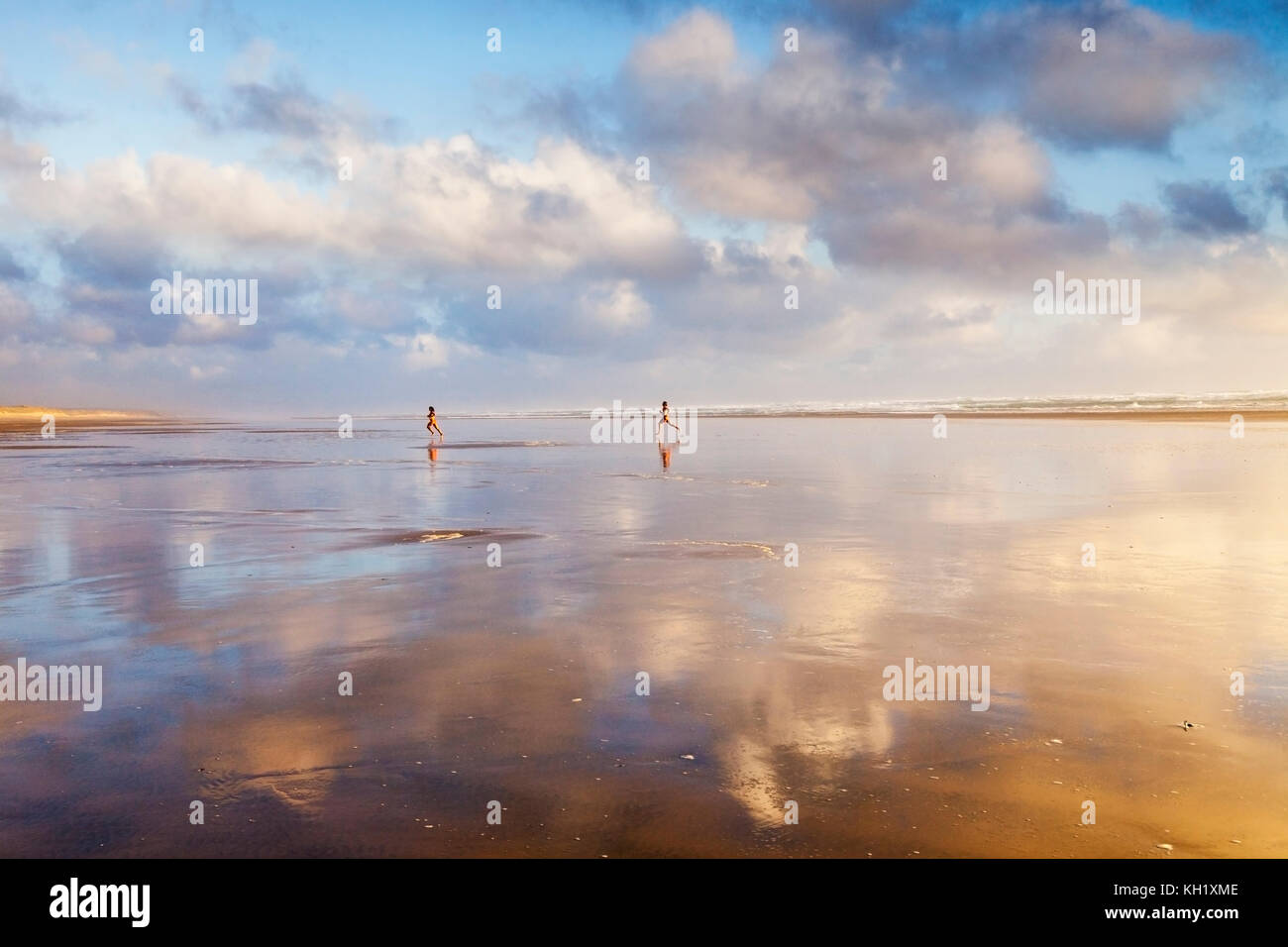 Young couple running over Ninety Mile Beach, Northland, New Zealand, at sunset. Stock Photo