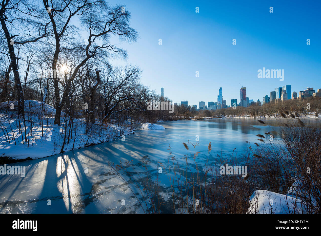 Scenic view of the Midtown skyline reflecting in the ice of the frozen Central Park lake the morning after a winter - Stock Image