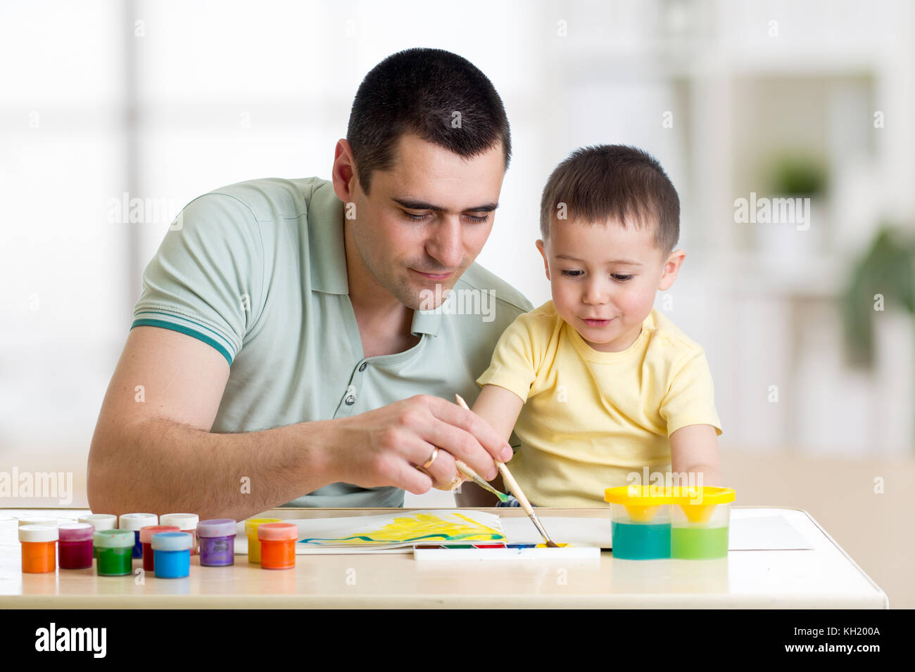 Father and child paint together. Dad teaches son how to paint correct and beautiful on paper. Family creativity - Stock Image