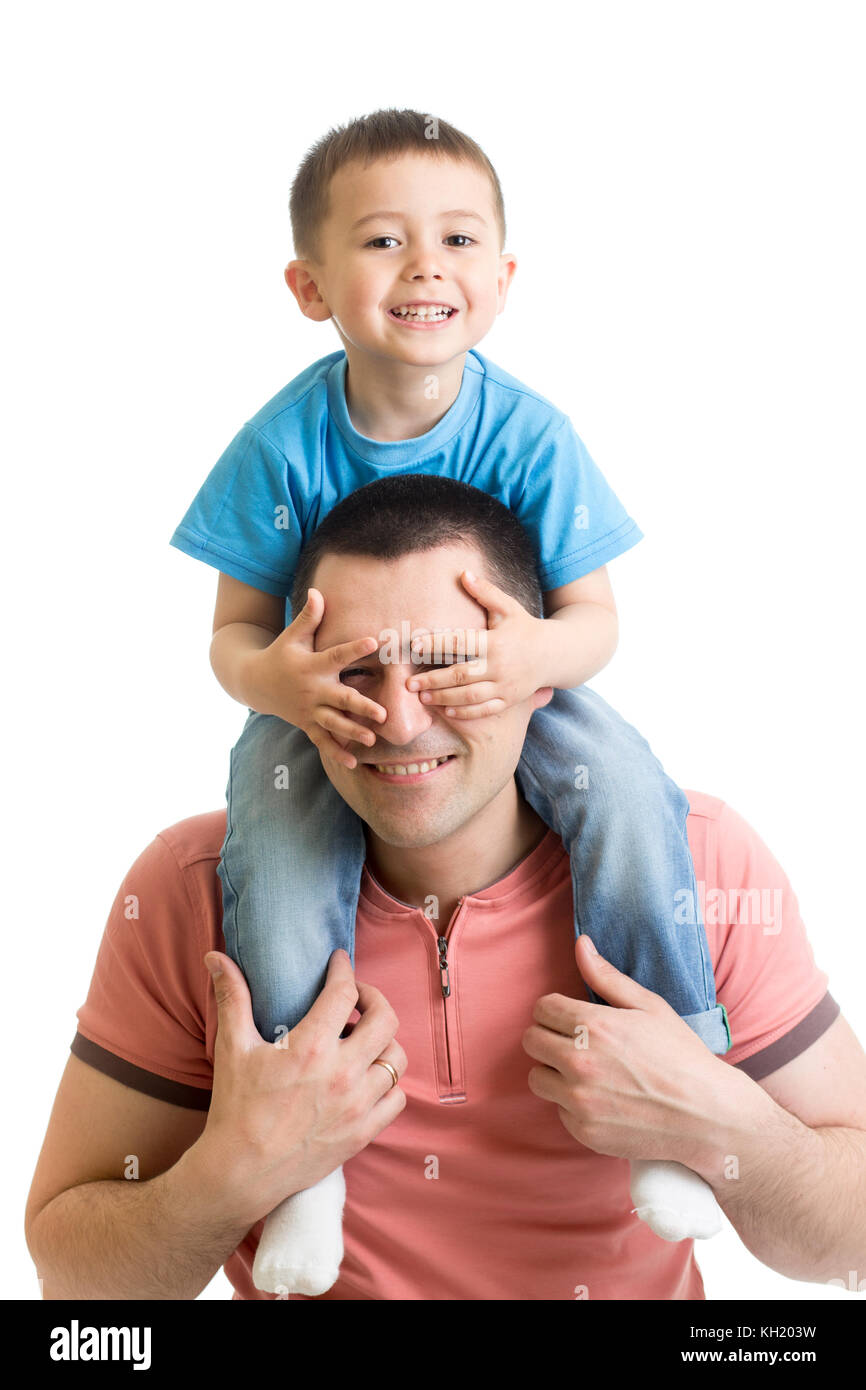 Child closes hands eyes father. Happy little boy enjoying with riding on father's back. Happy family portrait. - Stock Image