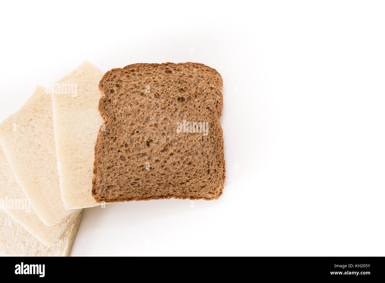 White no crust sandwich bread slices with one of them wholesome brown, on white background. - Stock Image