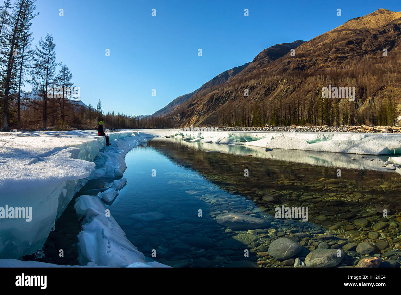 Girl sitting on the glacier ice melts in the spring on the river in the mountains. - Stock Image