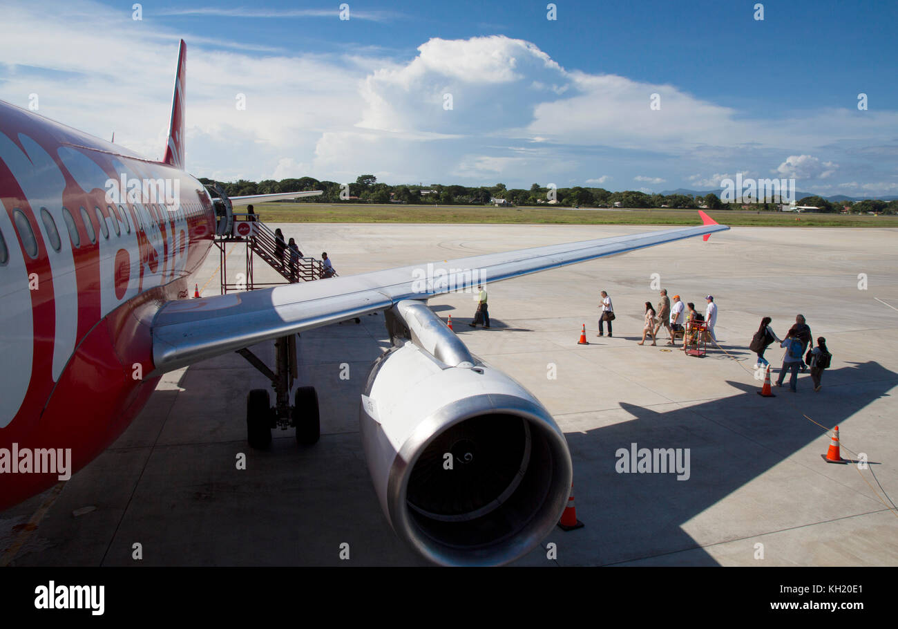 Air Asia Airbus A320 plane on tarmac with passengers boarding at Puerto Princesa, Palawan, Philippines - Stock Image
