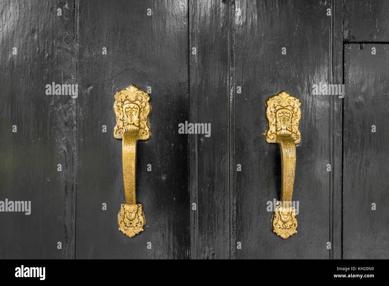 gold colored handle on black doors - Stock Image