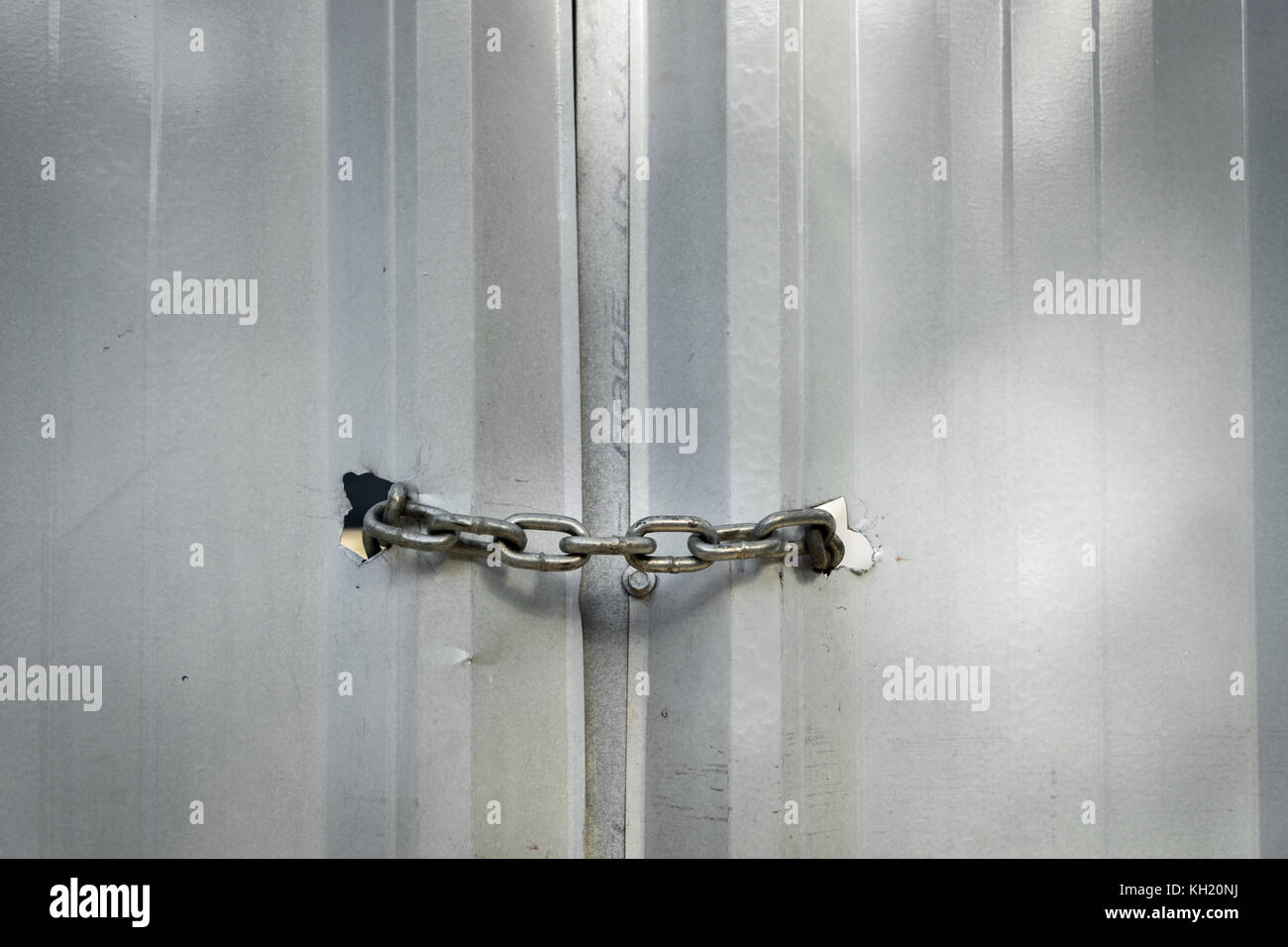 Metal chain securely locking door in an industrial setting - Stock Image
