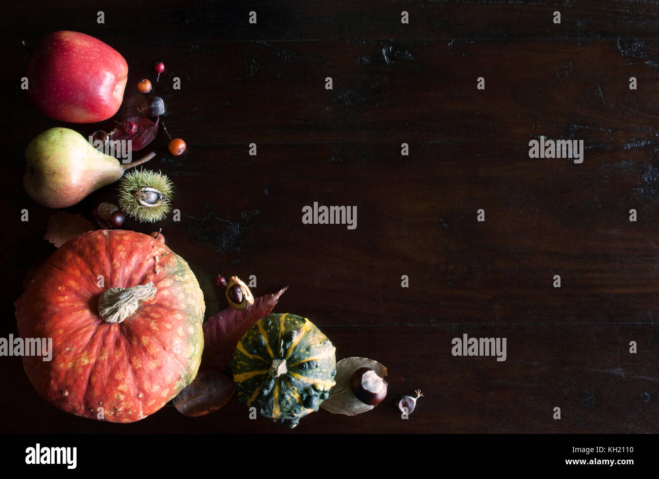 beautiful rustic fall flat lay with leaves, pumpkins and chestnuts on wooden background - Stock Image
