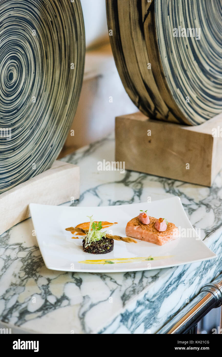 A salmon confit and quinoa salad dish placed upon a stone table with decorations in the background - Stock Image