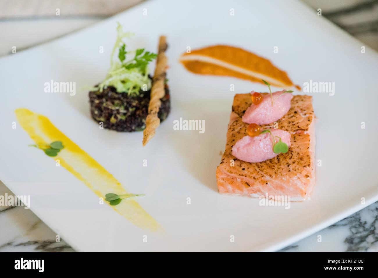 A close up of a salmon confit and quinoa salad dish - Stock Image
