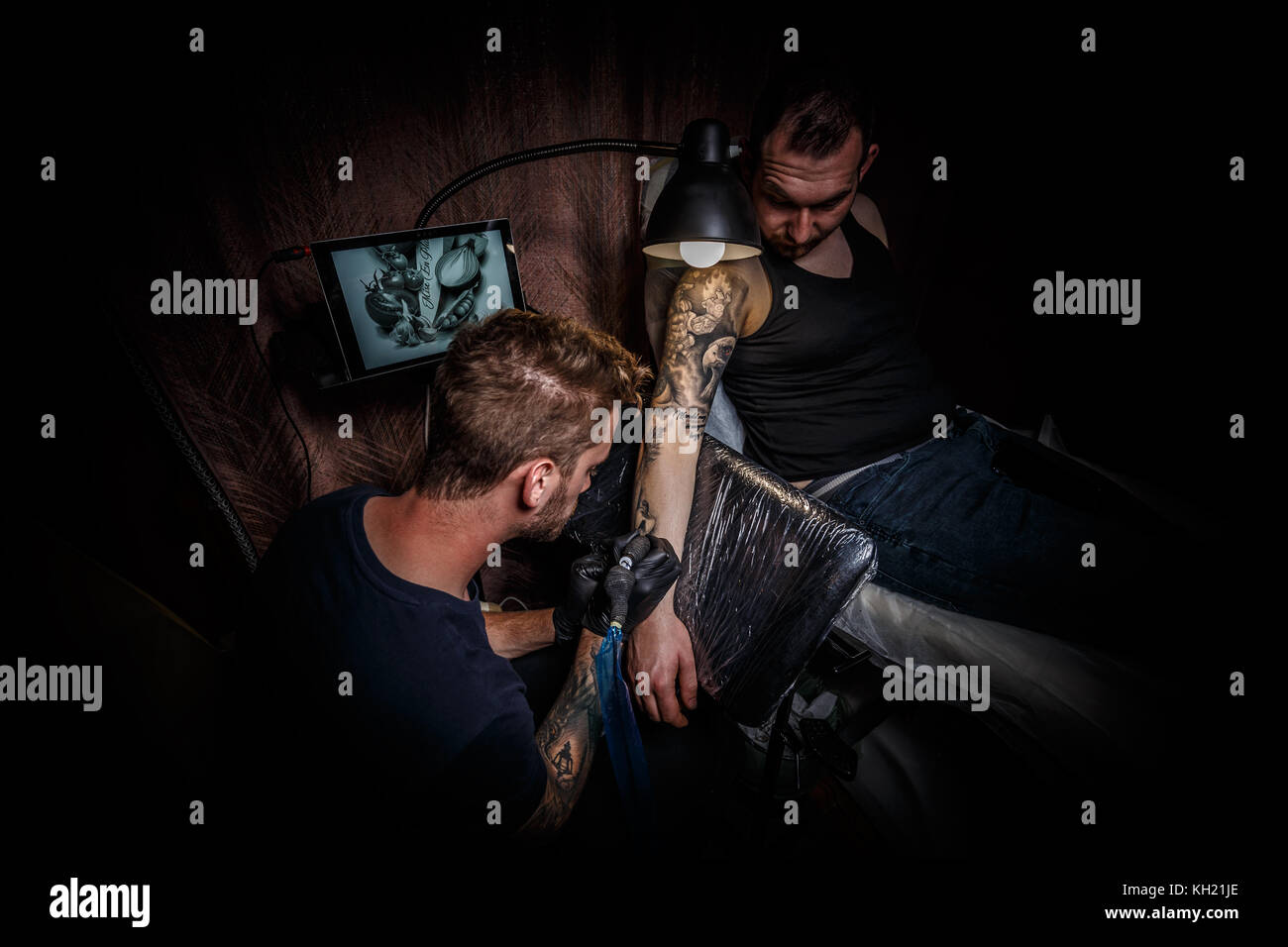 Portrait of a man tattoo master showing a process of tattoo creation in a man's hand under the lamplight - Stock Image