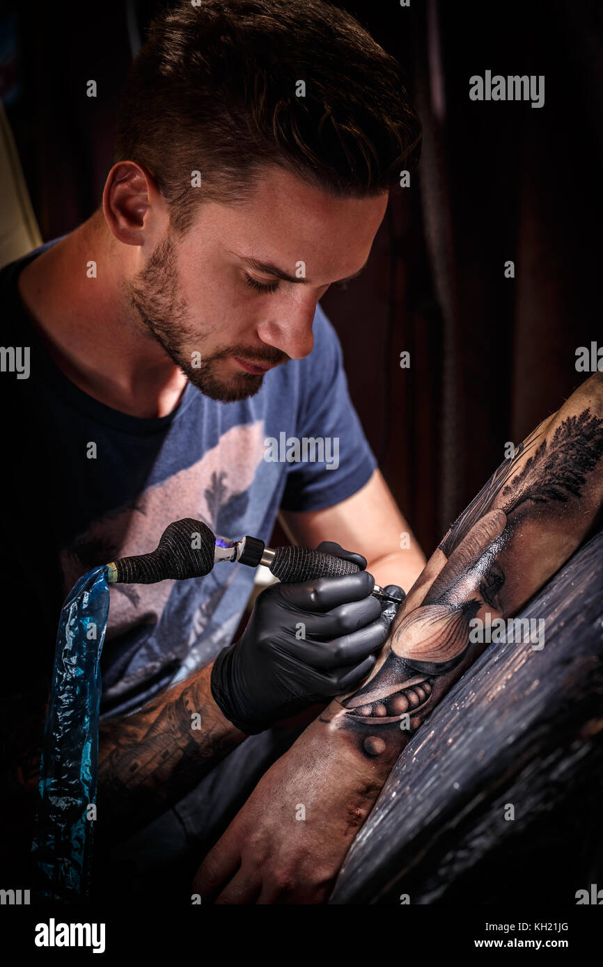 Professional tattoo artist makes a tattoo on a young man's hand - Stock Image