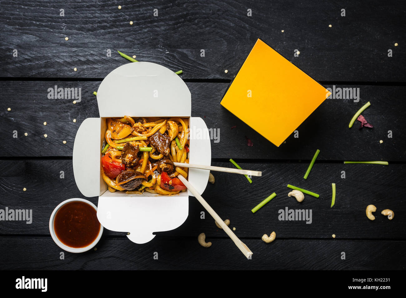 Udon stir fry noodles with meat and vegetables in a box on black background. With chopsticks and sauce. Top view. Stock Photo