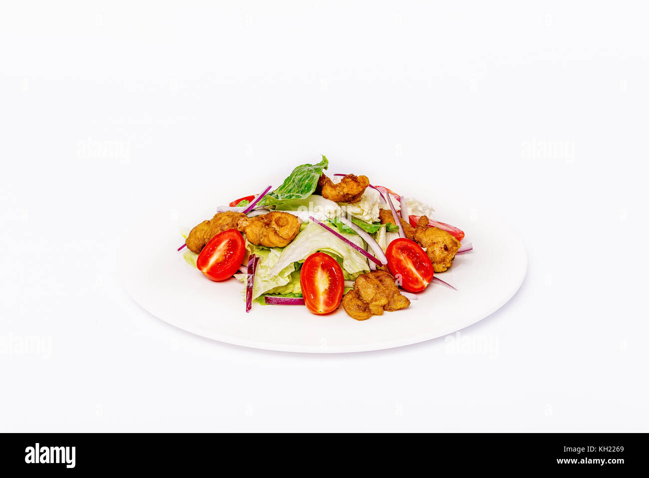 Pan-Asian salad, vegetables with fried chicken in batter. On a white plate on a white background. Stock Photo