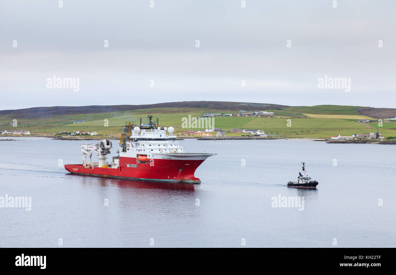 The multi purpose offshore vessel Fugro Symphony is pictured with the pilot boat, Knab off Lerwick on the Shetland - Stock Image