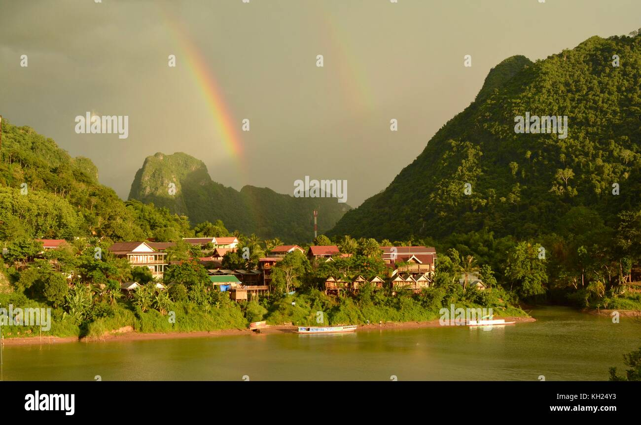 Rainbows above Nong Khiaw, Laos, in the early evening light - Stock Image