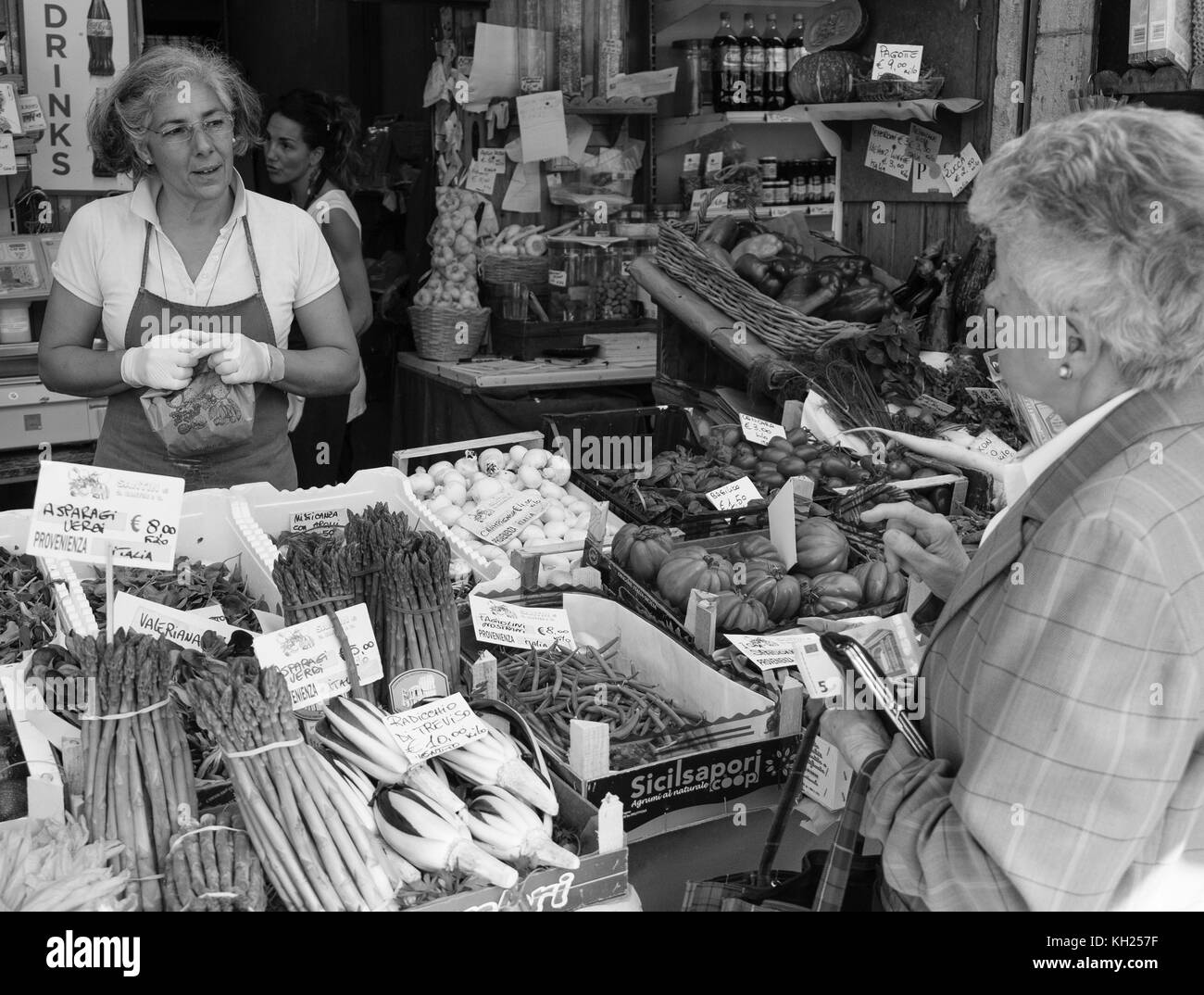 Two women converse at a market stand where fresh produce is being sold in Venice, Italy - Stock Image