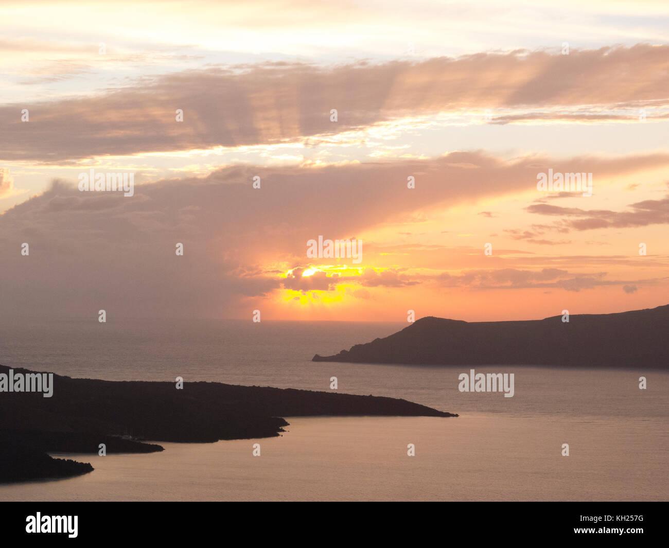 Setting sun over two landforms off the coast of Santorini, Greece, near the town of Oia - Stock Image