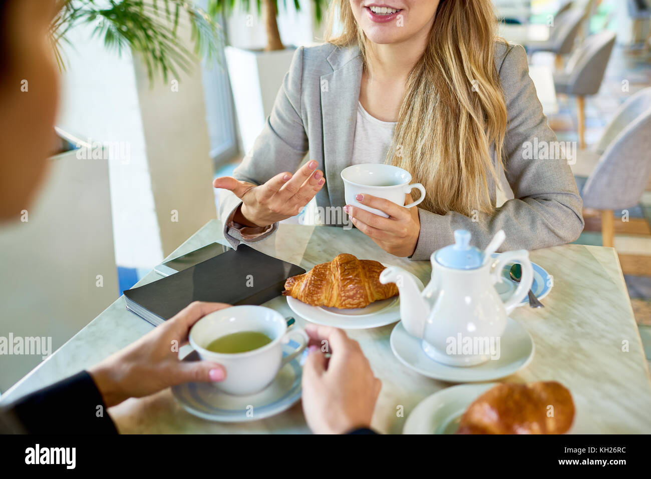 Portrait of two young women chatting gesturing actively during lunch break at cafe table with coffee and croissants - Stock Image