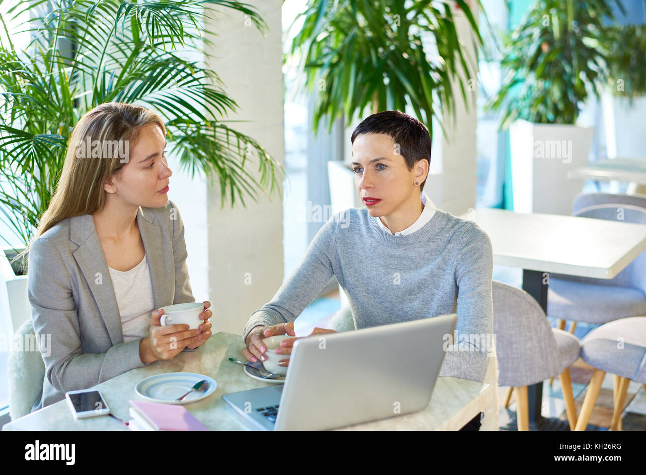 Portrait of successful businesswoman with short hair talking to female colleague discussing work and using laptop - Stock Image
