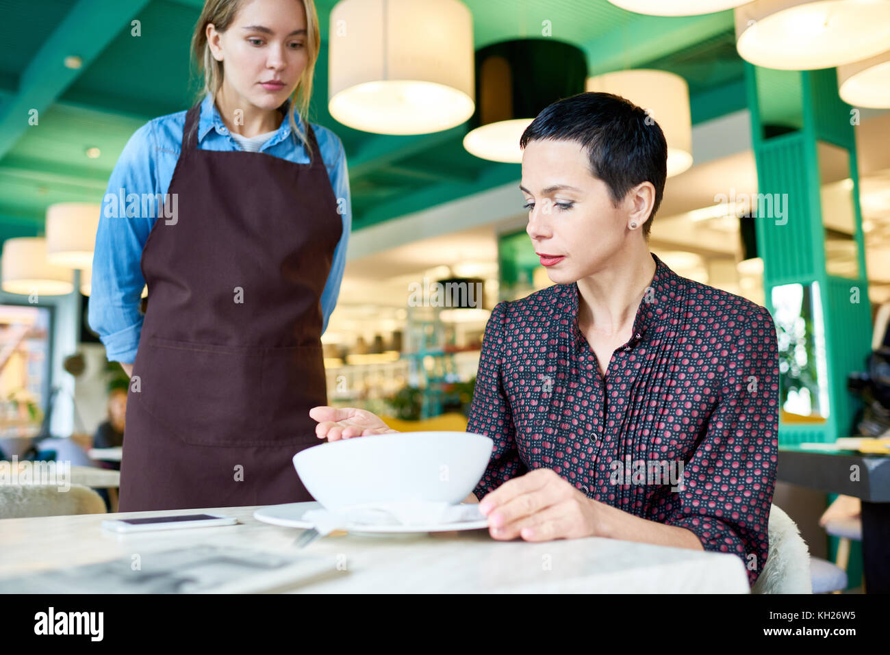 Portrait of elegant woman  complaining about food quality and taste to young waitress in cafe - Stock Image