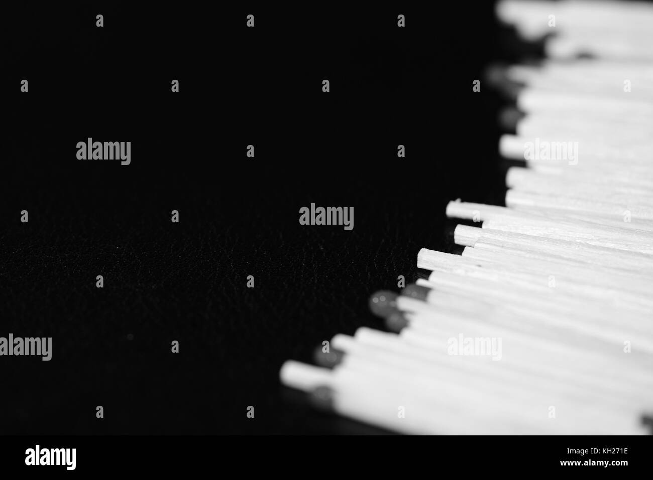 Scattered matches on dark background close up. Black and white - Stock Image