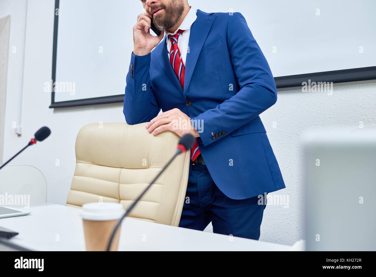 Mid section of unrecognizable bearded businessman seaking by phone waiting for press conference meeting in business - Stock Image