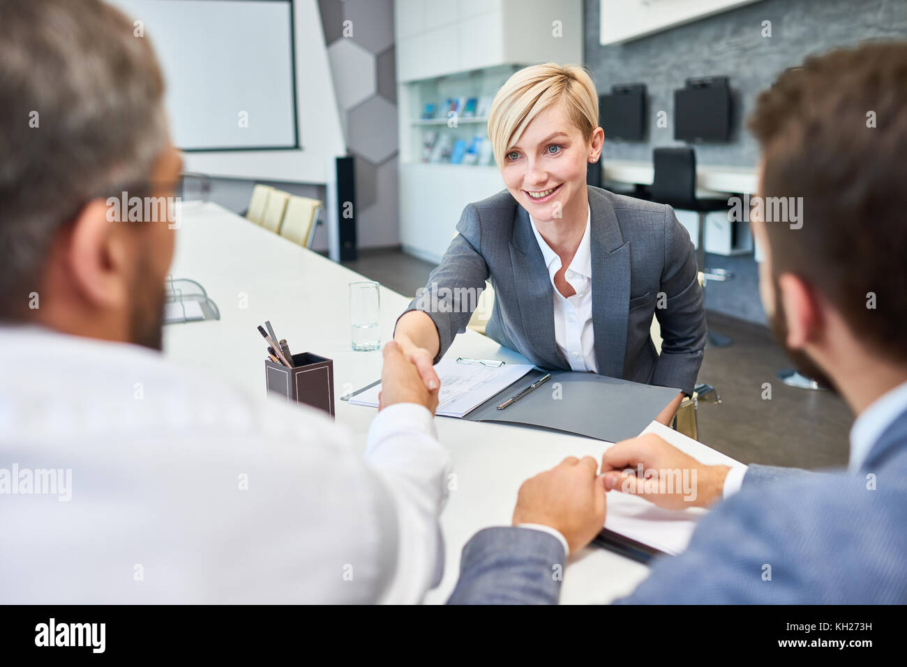 Portrait of young successful businesswoman shaking hands with partners at meeting table in board room after successful - Stock Image