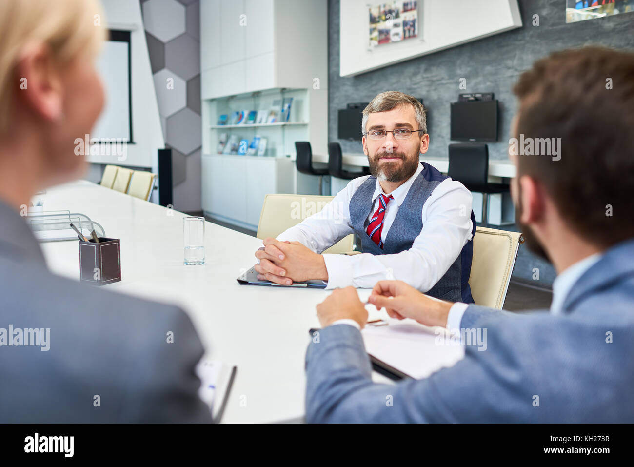 Portrait of barded mature businessman listening  to partners sitting at meeting table in board room while negotiating - Stock Image