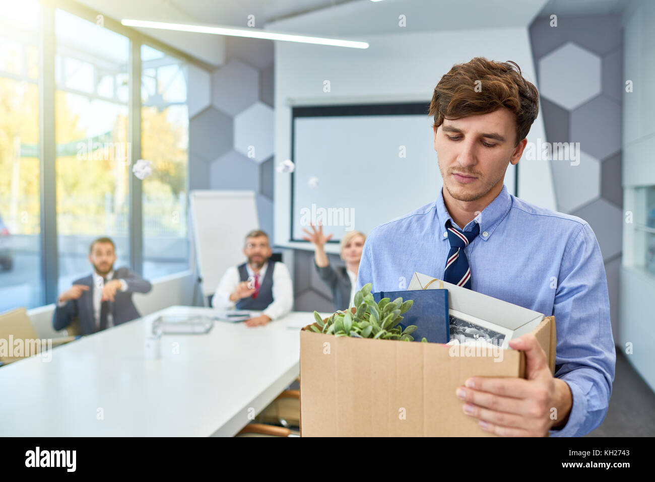 Portrait of sad young man holding box of personal belongings being fired from work in business company, copy space - Stock Image