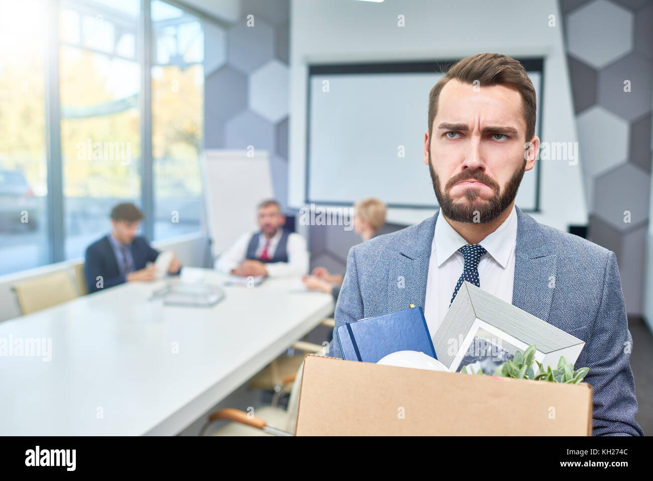 Portrait of sad bearded businessman holding box of personal belongings being fired from work in company, copy space - Stock Image
