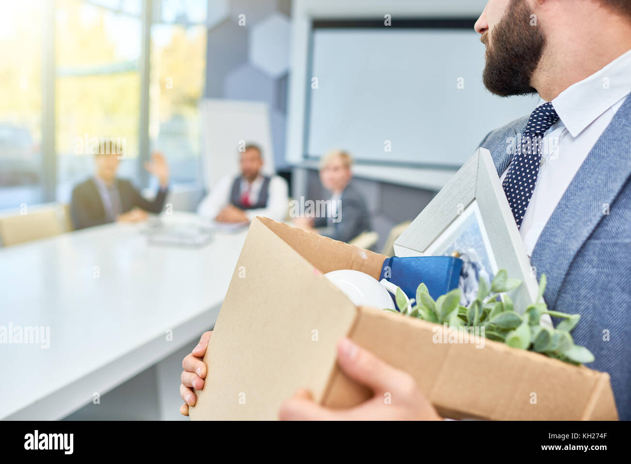 Unrecognizable man holding box of personal belongings looking back at several business people who fired him - Stock Image