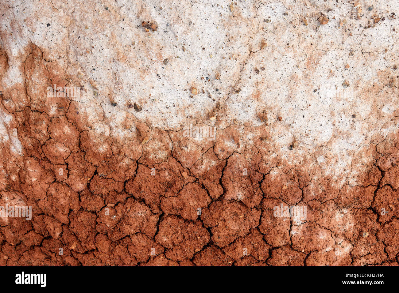 Abstract background with texture of brown and white colors of dry ground with cracks and stones on the mountain - Stock Image