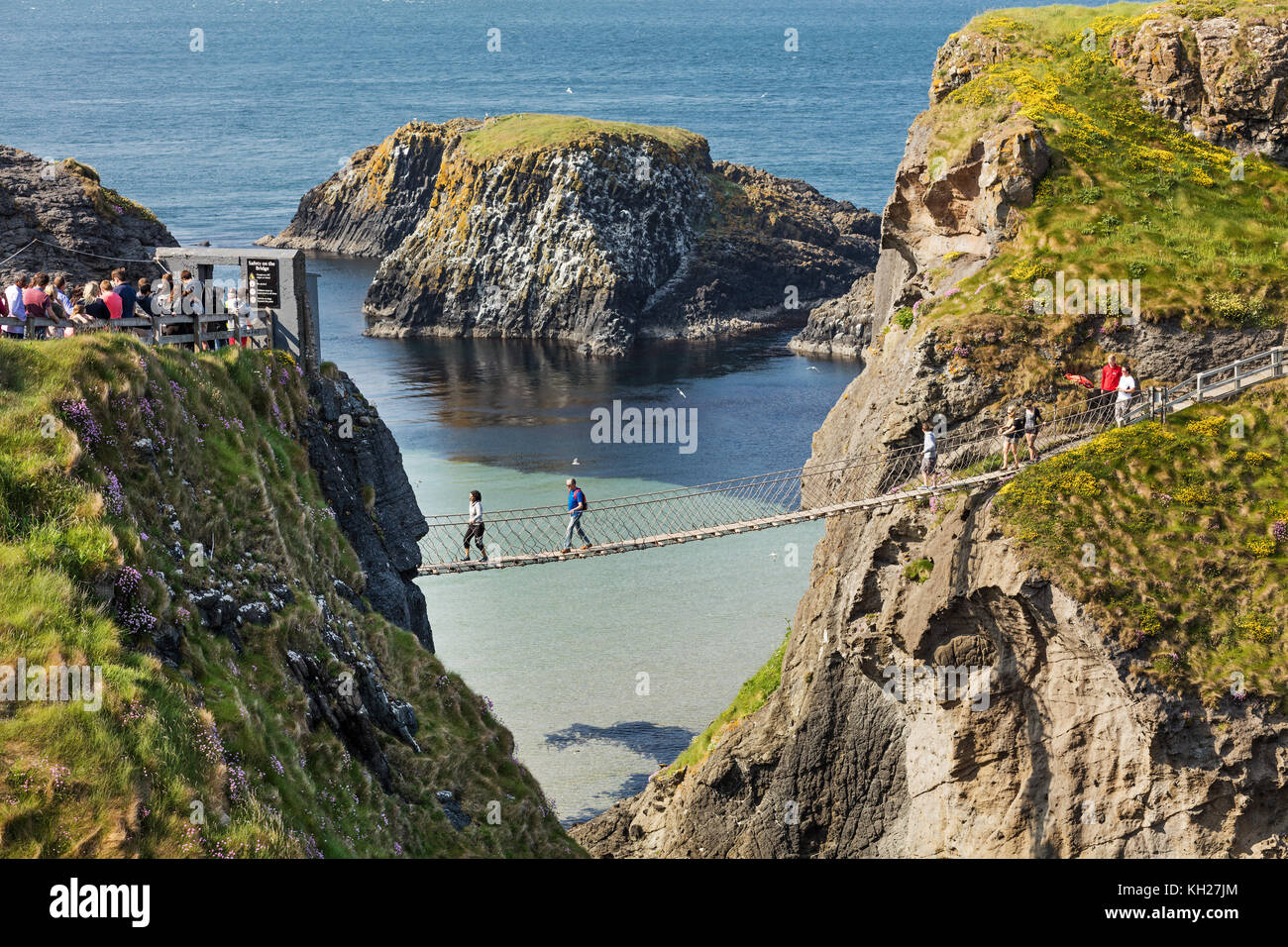 Thousands of tourists visiting Carrick-a-Rede Rope Bridge in County Antrim of Northern Ireland, hanging 30m above - Stock Image