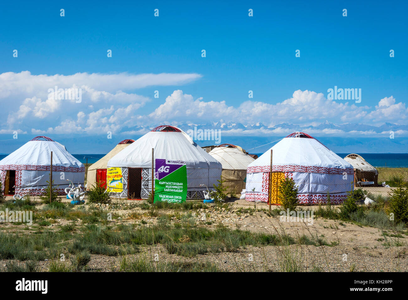 KYZYL TOO, KYRGYZSTAN - AUGUST 8: Yurts next to Karakol lake with the advertizing for local mobile data providers. - Stock Image