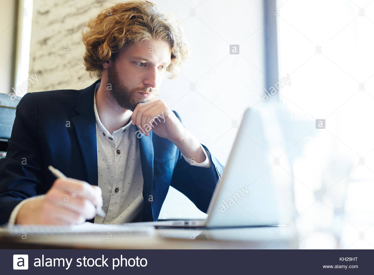 Pensive young man looking at online data in front of laptop - Stock Image