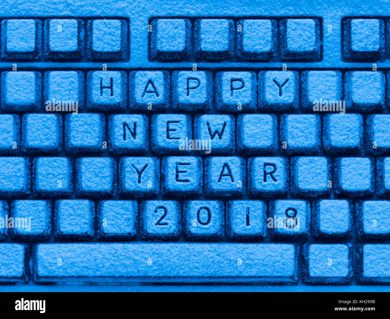 illuminated with blue light computer keyboard with inscription happy new year 2018 covered with snow Stock Photo
