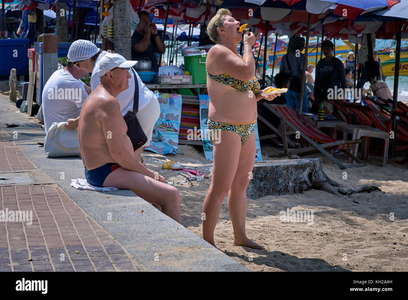 Mature woman in a bikini. Couple in swimwear at the beach. - Stock Image