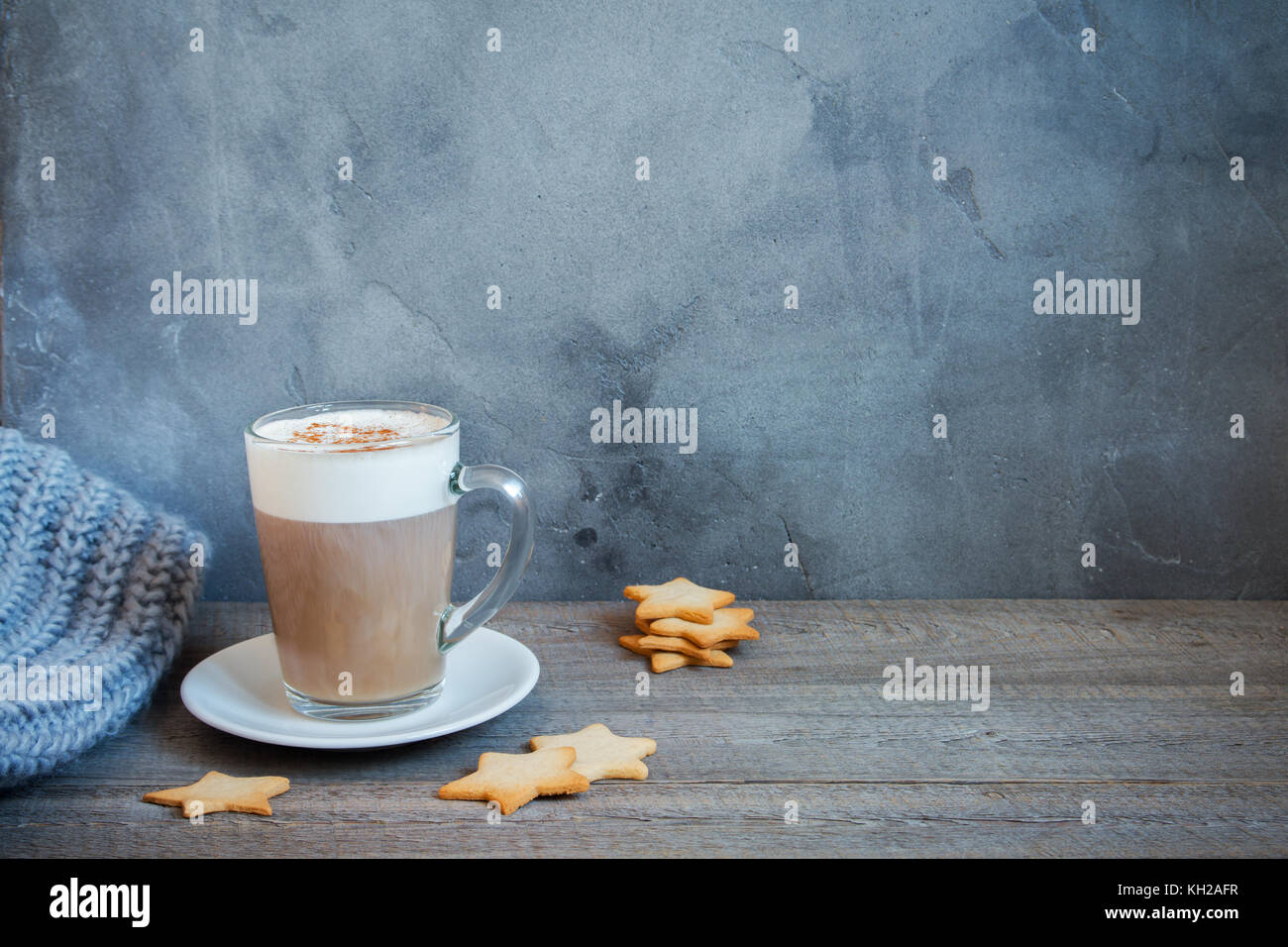 Winter latte coffee with star shaped christmas cookies  and warm scarf. Christmas and winter holidays cozy still - Stock Image