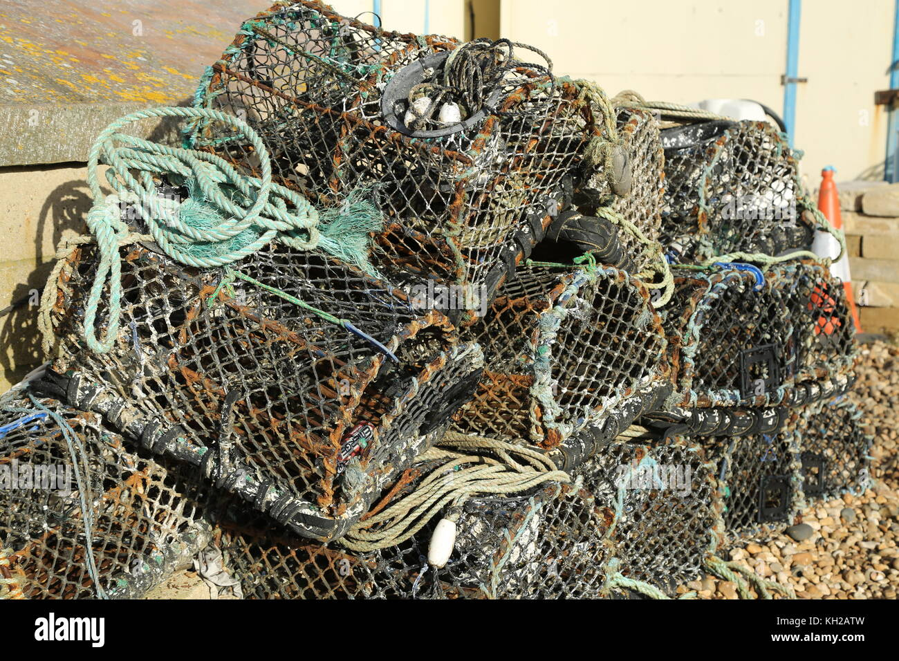Fishermen's lobster pots stacked on the shingle beach in Bognor Regis, West Sussex, UK. Used by fishermen to - Stock Image