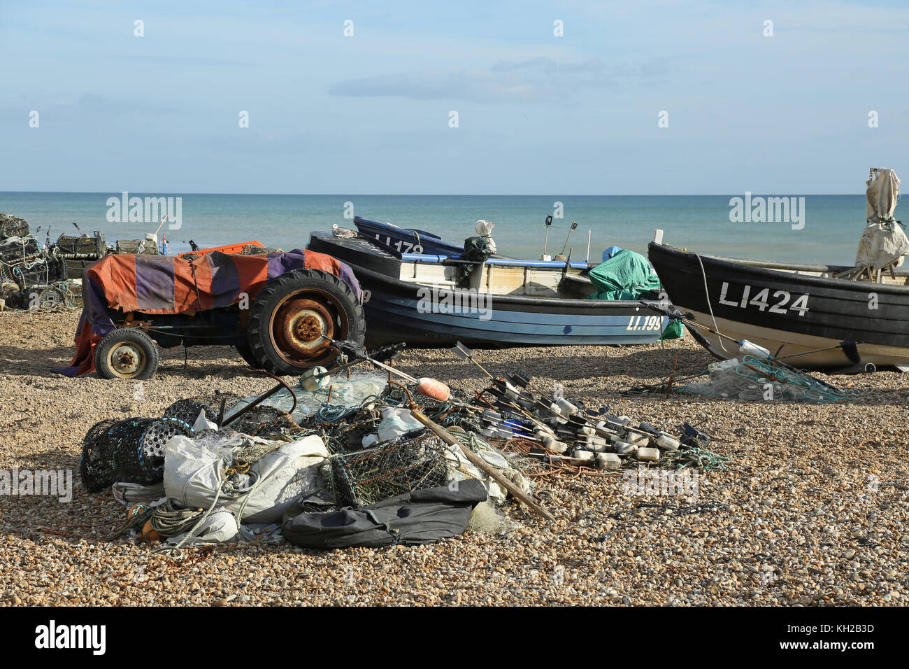 Open fishing boats pulled up on the shingle of Bognor beach, west Sussex, UK. Shows nets and lobster pots piled - Stock Image