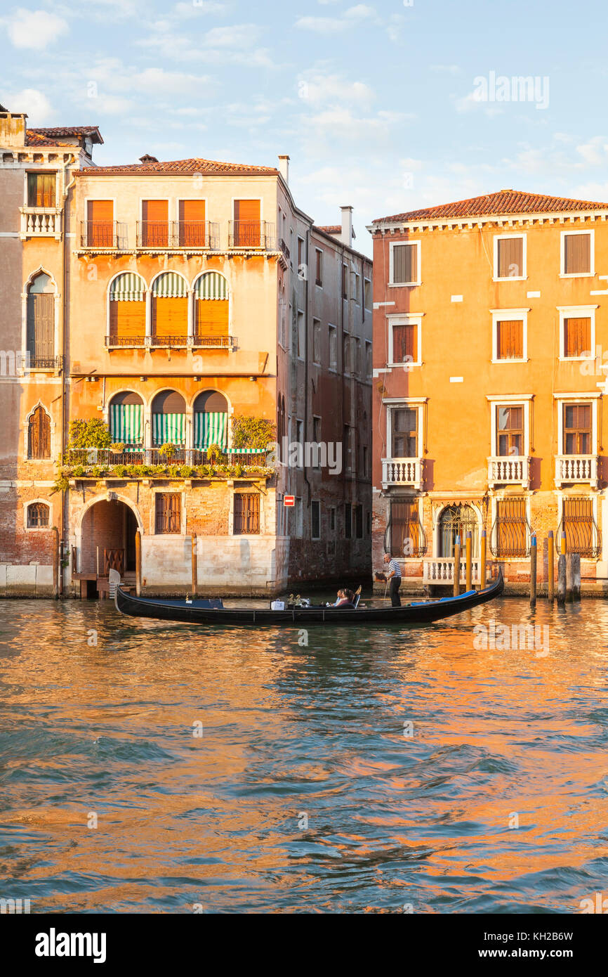 Gondola on the Grand Canal at sunset, Cannaregio, Venice, Italy rowing tourists past Palazzo Bollani Erizzo in golden - Stock Image