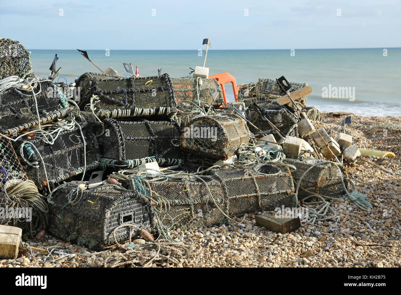 Fishermen's lobster pots piled up on the shingle beach in Bognor Regis, West Sussex, UK. Sunny, winter day. - Stock Image