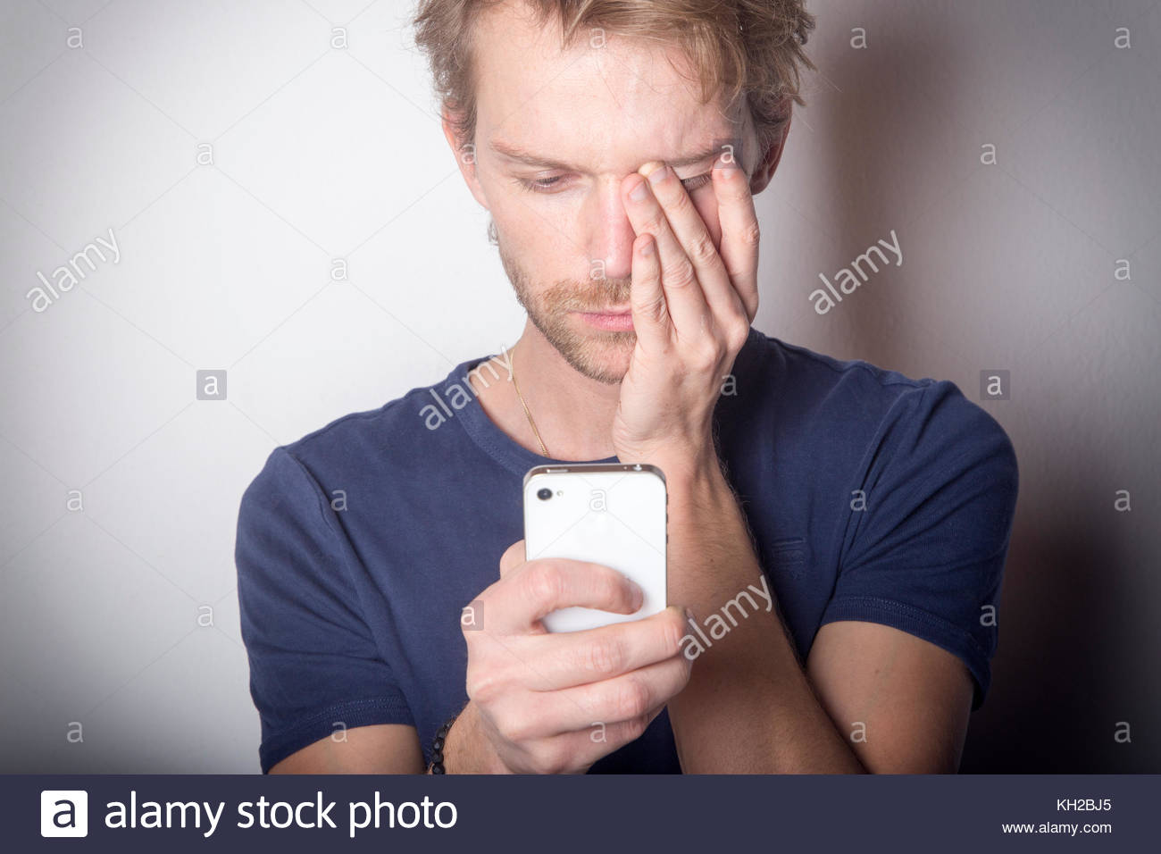 Young man using smartphone looking depressed - Stock Image