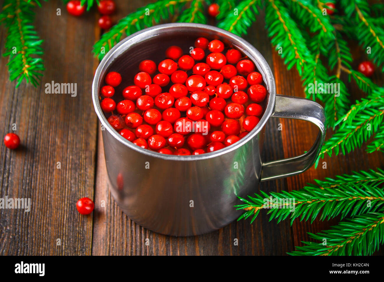 Morse or tea from cowberry in a tin mug, surrounded by fir branches on a wooden table - Stock Image