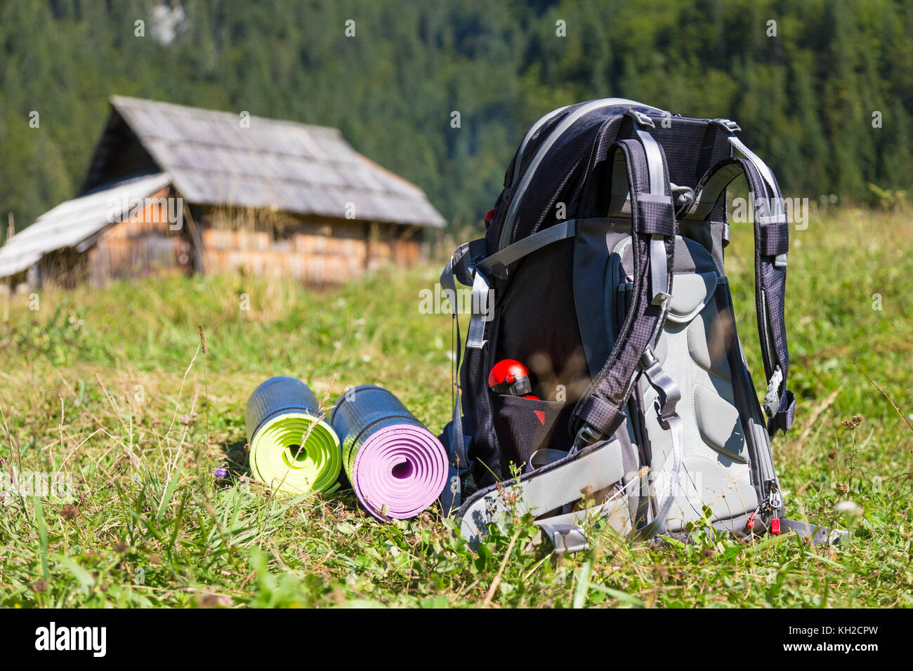 Backpack and yoga mats on mountain meadow. - Stock Image