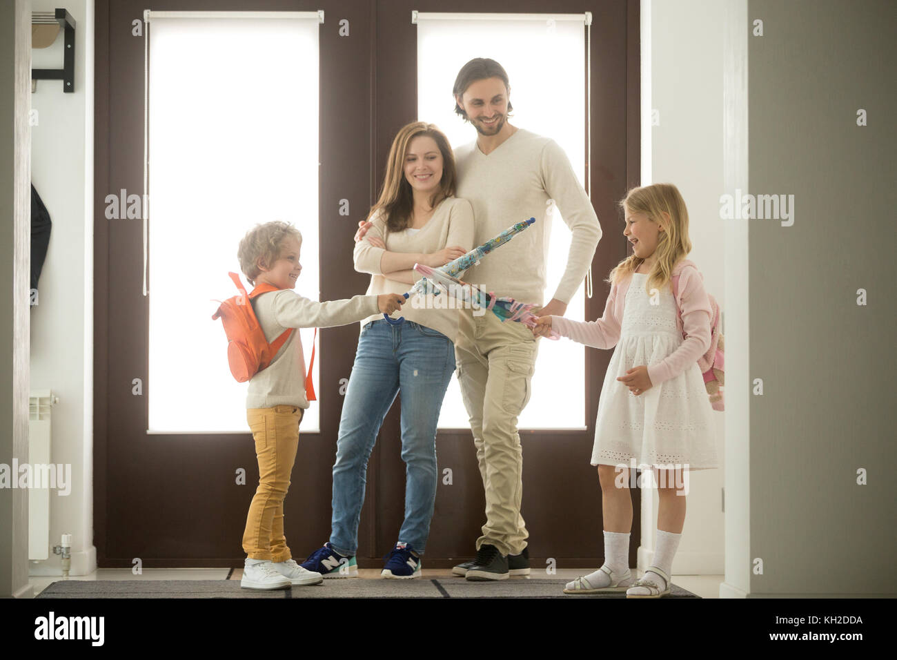 Sister and brother play umbrellas, kids boy and girl having fun standing at hallway, happy family of four spending - Stock Image