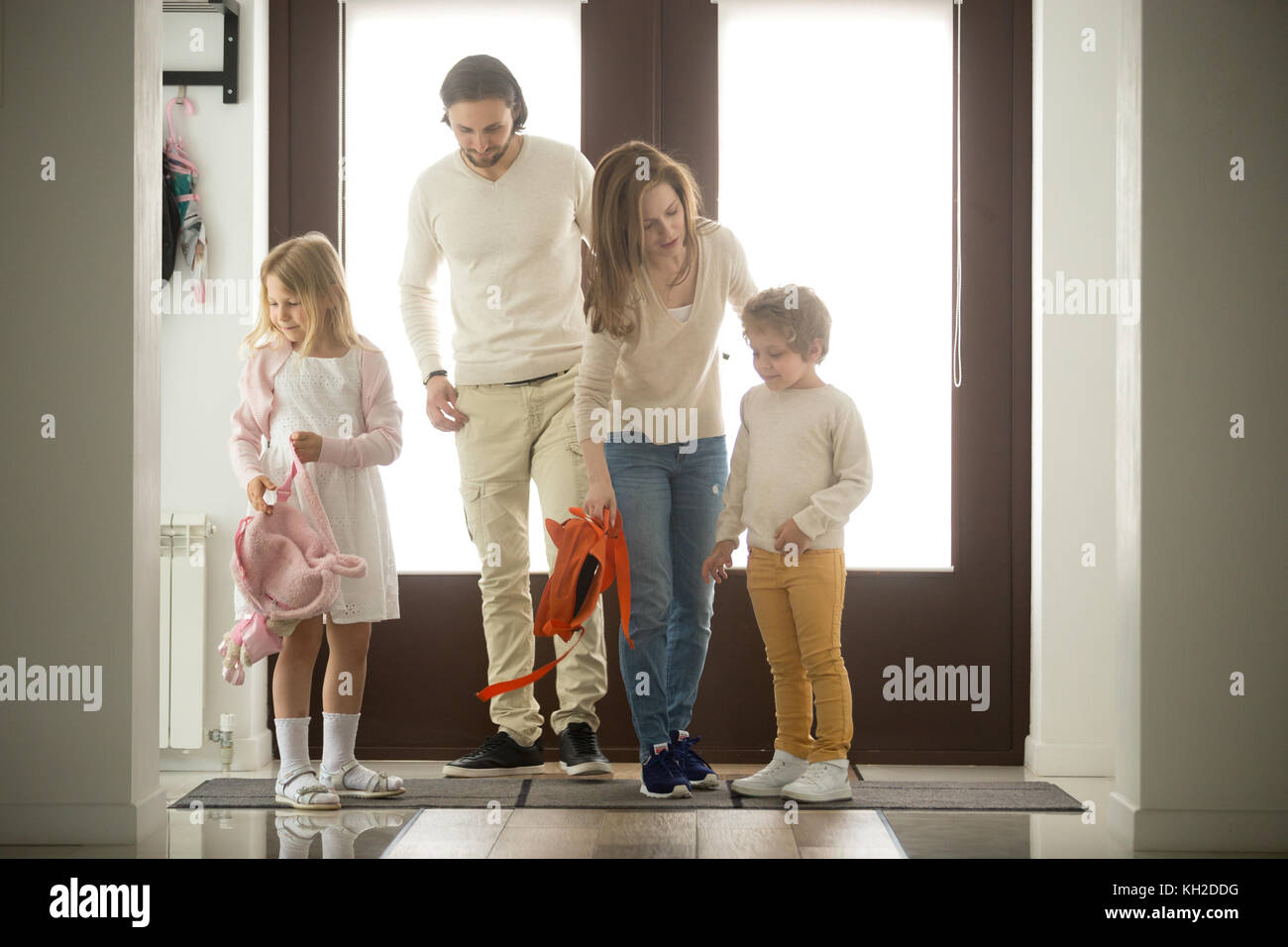Children siblings returning sweet home with parents, happy family of four coming back to house after walking together - Stock Image
