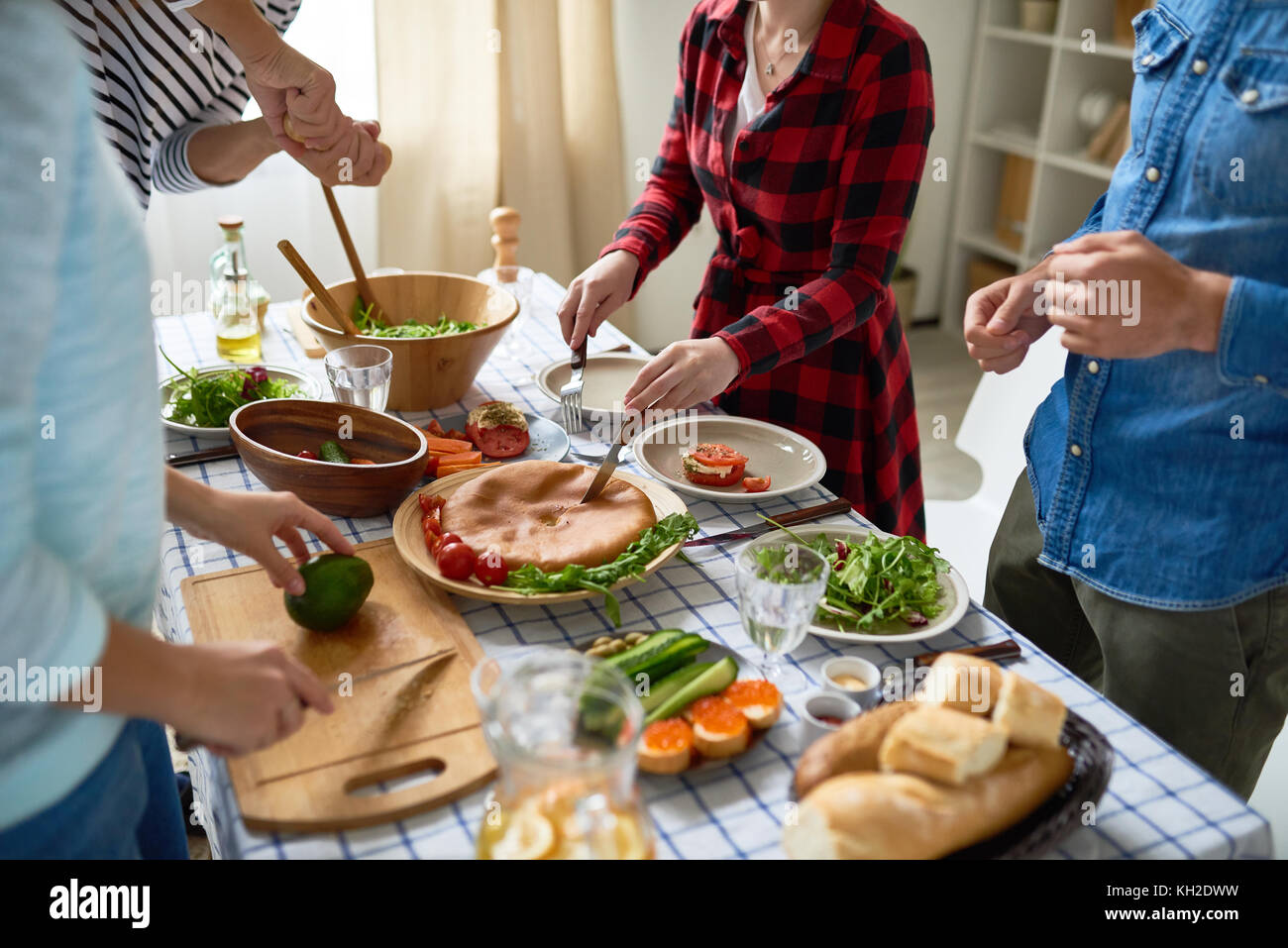 Low section of unrecognizable people cutting pie and vegetables standing around dinner table with homemade food - Stock Image