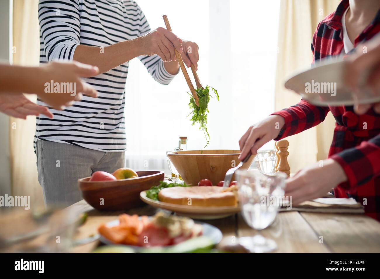 Side view mi-section of group of people standing at festive dinner table serving homemade food to plates during - Stock Image