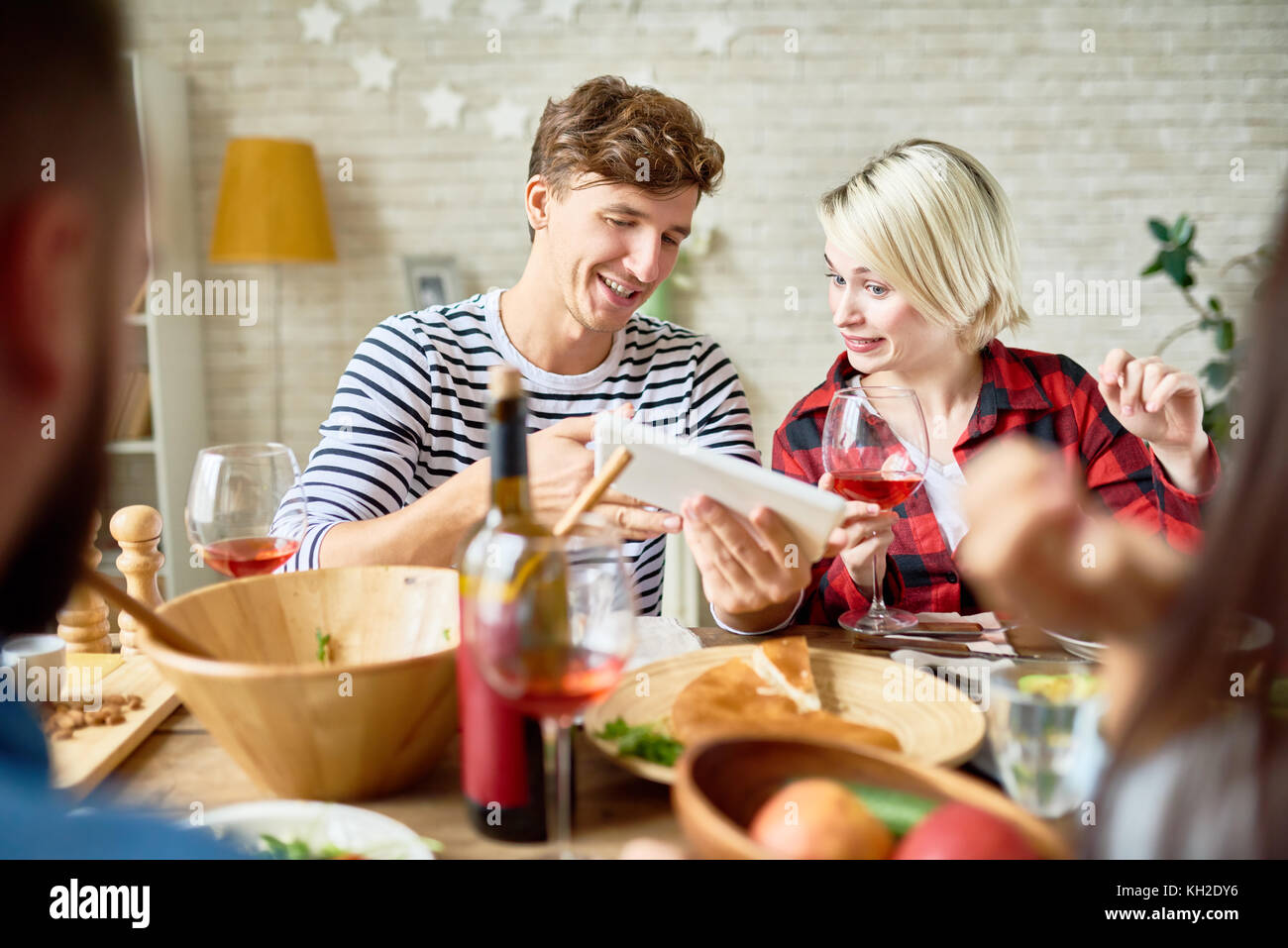 Portrait of young man and woman looking at digital tablet discussing photos while having dinner with friends sitting - Stock Image