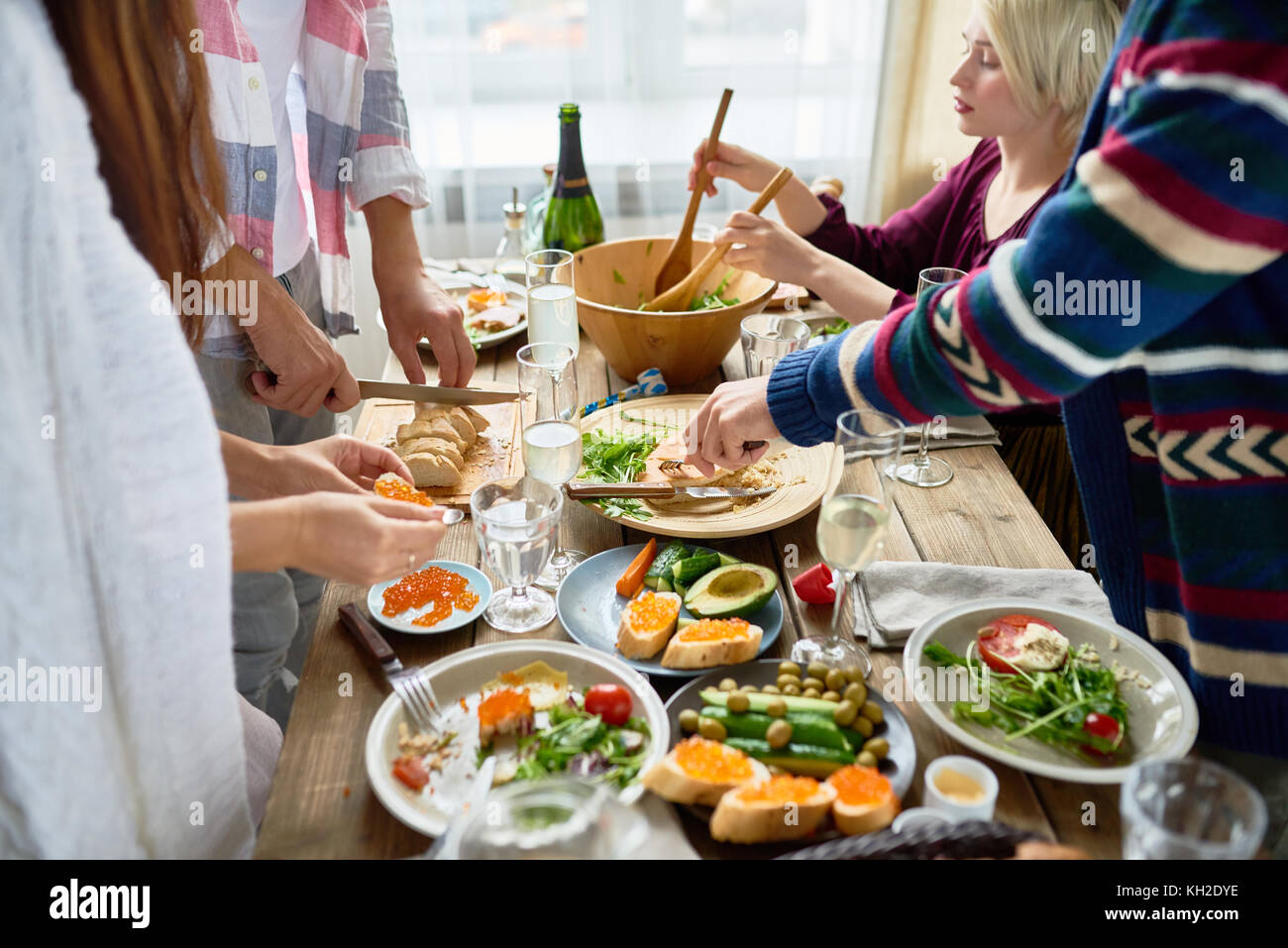 Mid-section group of young people preparing dinner for festive celebration standing at big table and making dishes - Stock Image